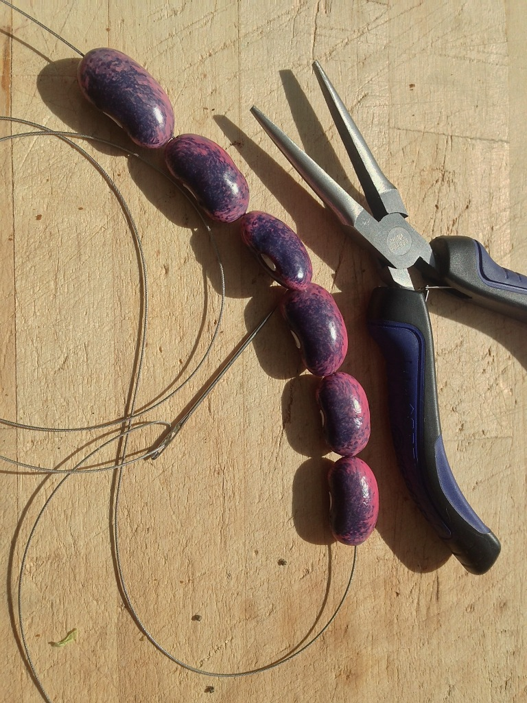 Thread a darning needle with stiff thread or a flexible wire.